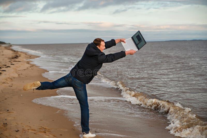 Het conceptenwerk en rust kwesties De mens freelancer werpt laptop in het overzees stock afbeeldingen