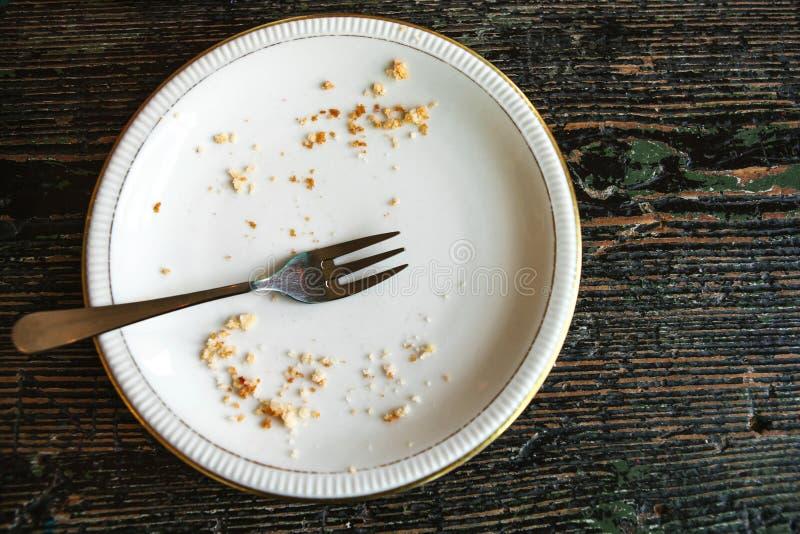 Het conceptuele beeld van het eind van de vakantie is een lege plaat met crumbs en een vork op het royalty-vrije stock afbeelding