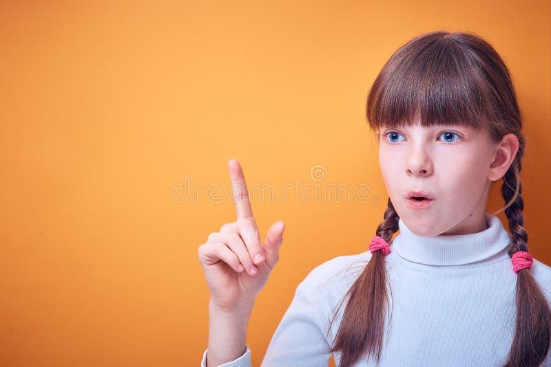 Het conceptuele idee, Kaukasisch tienermeisje toont wijsvinger op gekleurde achtergrond, plaats voor tekst royalty-vrije stock fotografie