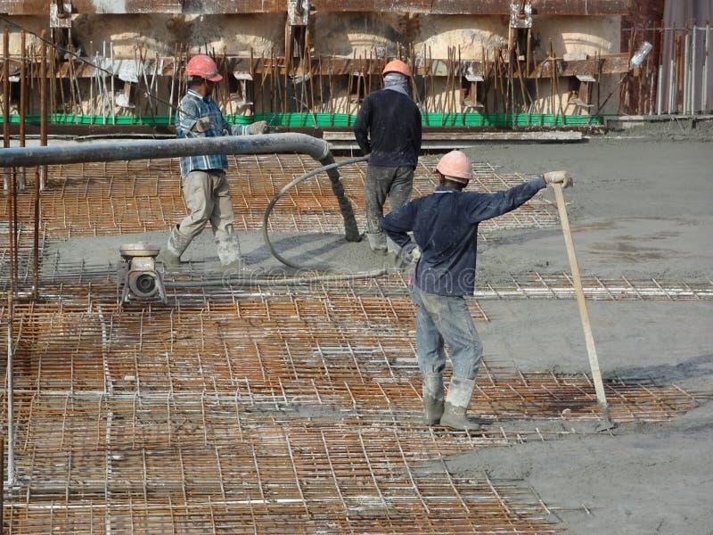Het Concretingswerk door bouwvakkers bij de bouwwerf stock foto's
