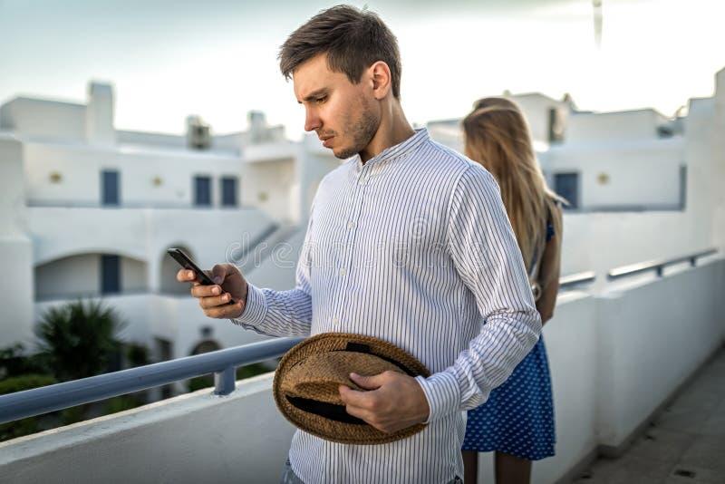 Het conflict van het familiepaar tussen echtgenoot en vrouw De kerelmens kijkt smartphone of wijzerplaten stock foto