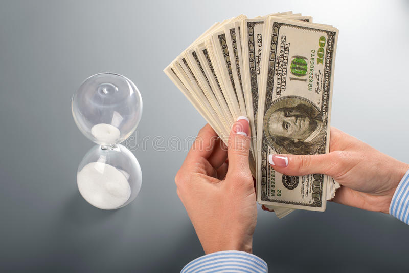 Het contante geld en de zandloper van de onderneemster royalty-vrije stock foto