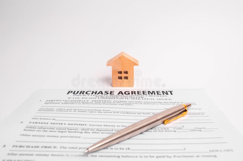 Het contract van aankoop en blokhuis op een witte achtergrond Het concept het kopen en onroerende goederen verkopen, besluiten ga royalty-vrije stock afbeelding