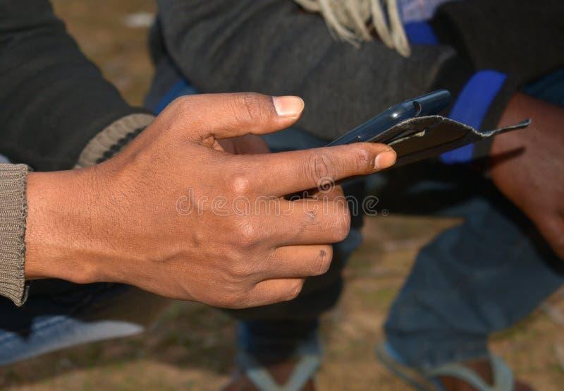 Het controleren van de app van de mobiele telefoon in de winter in een plattelandsstad stock afbeeldingen