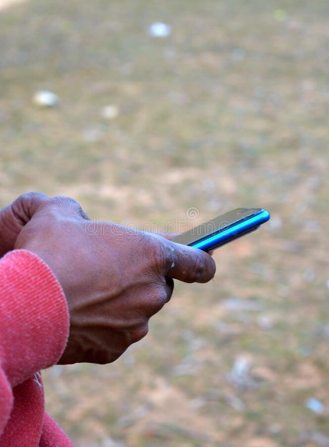 Het controleren van de app van de mobiele telefoon in de winter in een plattelandsstad royalty-vrije stock afbeelding