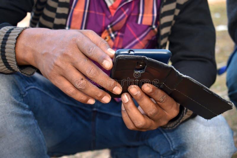 Het controleren van de app van de mobiele telefoon in de winter in een plattelandsstad stock afbeelding