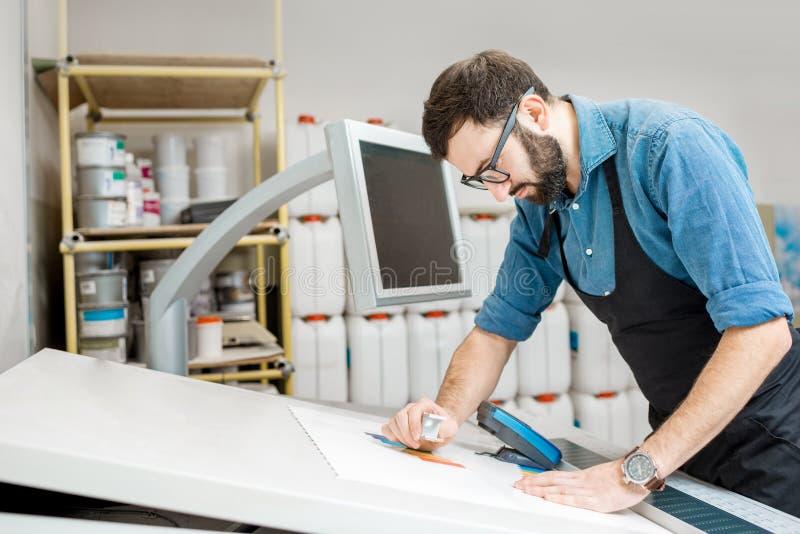 Het controleren van de kwaliteit van de druk met vergrootglas stock afbeelding