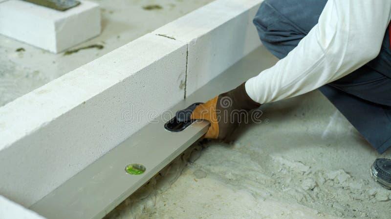 Het controleren van gelijkheid van geluchte concrete muur met waterpas royalty-vrije stock foto's