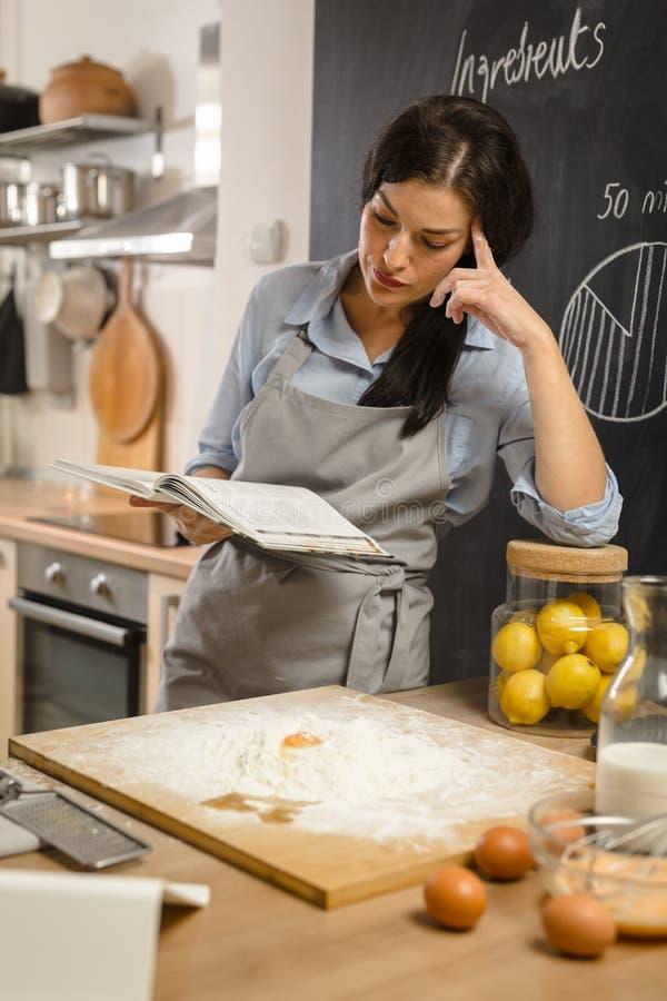 Het controleren van recept in kookboek Vrouw die Amerikaanse pastei voorbereiden stock afbeeldingen