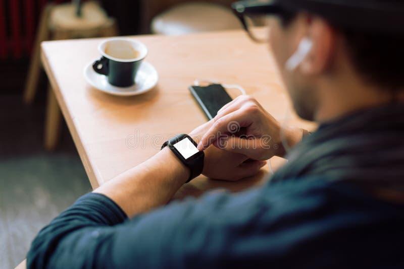 Het controleren van zijn smartwatch royalty-vrije stock afbeeldingen