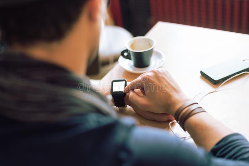 Het controleren van zijn smartwatch stock foto
