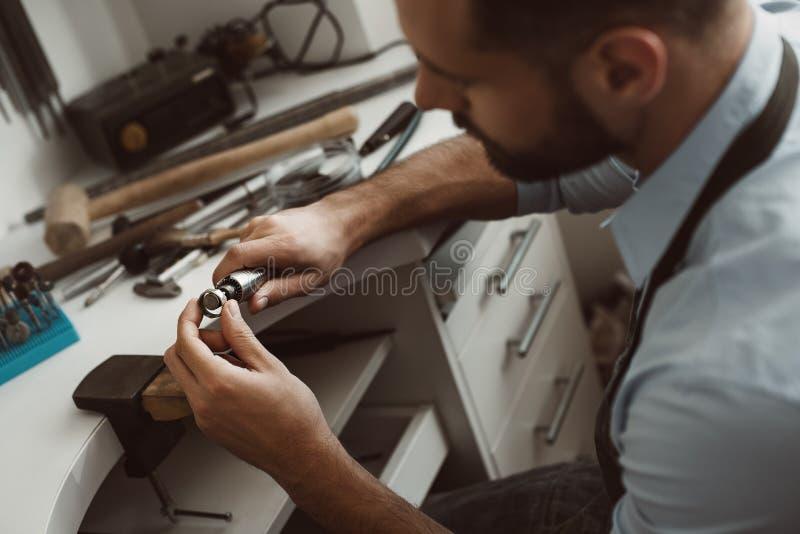 Het creëren van art. Close-upfoto van mannelijke juwelier die een nieuwe zilveren ring maken bij zijn werkbank royalty-vrije stock fotografie