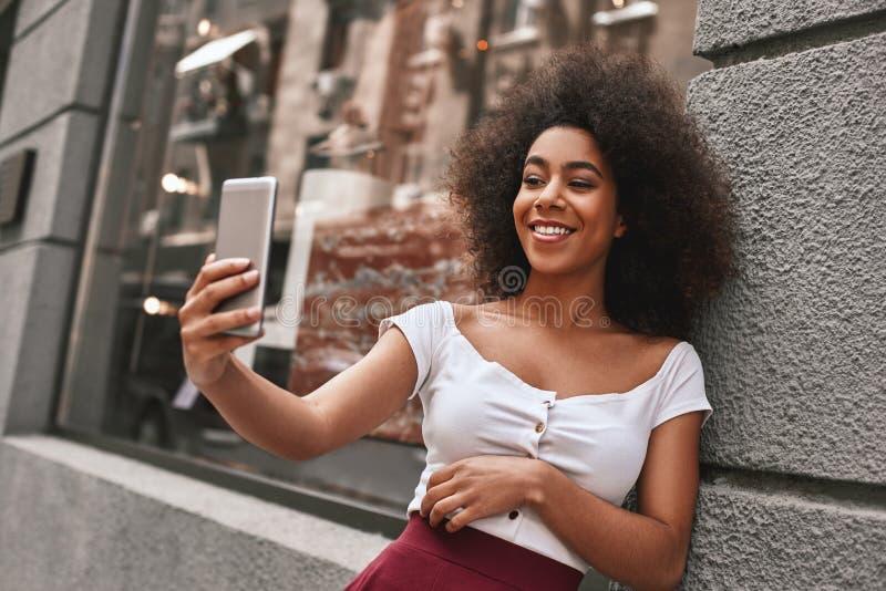 Het creëren van gelukkig geheugen De aantrekkelijke en jonge Amerikaanse vrouw die van Afro selfie terwijl het doorbrengen van ti royalty-vrije stock afbeelding