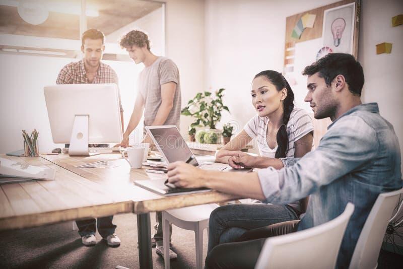Het creatieve commerciële team verzamelde zich rond laptops stock foto's