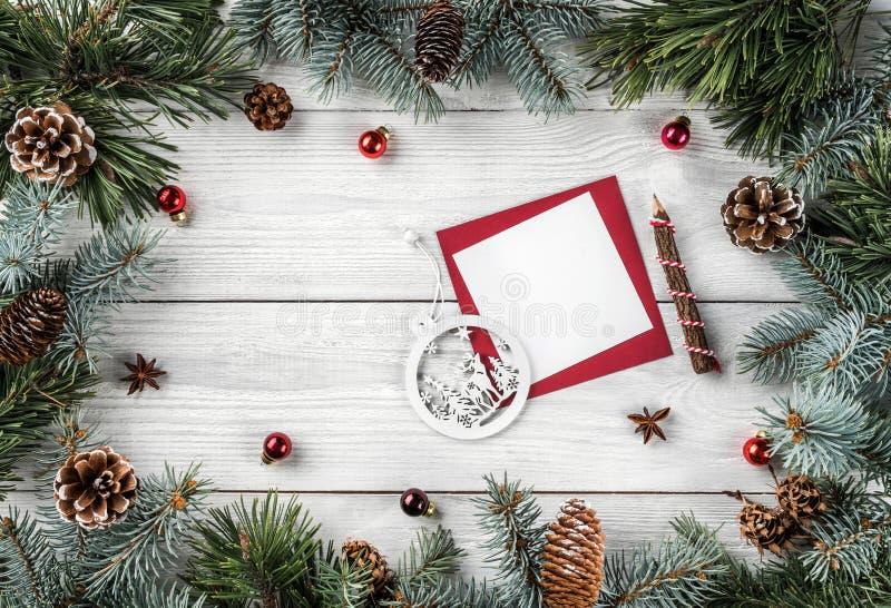 Het creatieve die kader van Kerstboom wordt gemaakt vertakt zich op witte houten achtergrond met document kaartnota, denneappels, stock foto's