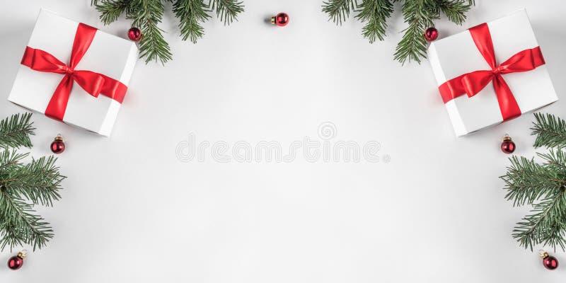 Het creatieve die kader van Kerstmisspar wordt gemaakt vertakt zich op Witboekachtergrond met rode decoratie, denneappels royalty-vrije stock afbeeldingen
