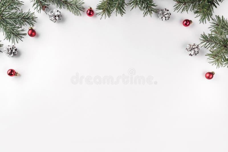 Het creatieve die kader van Kerstmisspar wordt gemaakt vertakt zich op witte achtergrond met rode decoratie, denneappels royalty-vrije stock afbeelding