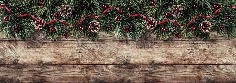 Het creatieve die lay-outkader van Kerstmisspar wordt gemaakt vertakt zich, denneappels en rode decoratie op houten achtergrond K stock afbeeldingen
