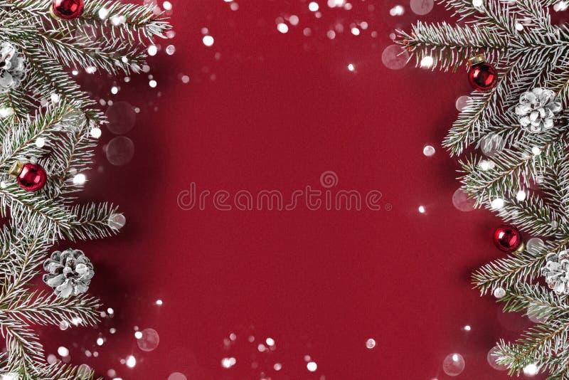 Het creatieve die lay-outkader van Kerstmisspar wordt gemaakt vertakt zich, denneappels, giften, rode decoratie op rode achtergro royalty-vrije stock foto
