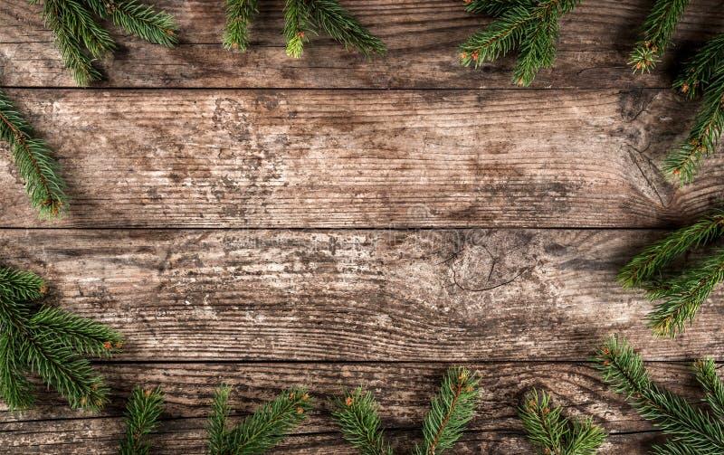 Het creatieve die lay-outkader van Kerstmisspar wordt gemaakt vertakt zich, denneappels op houten achtergrond stock foto's