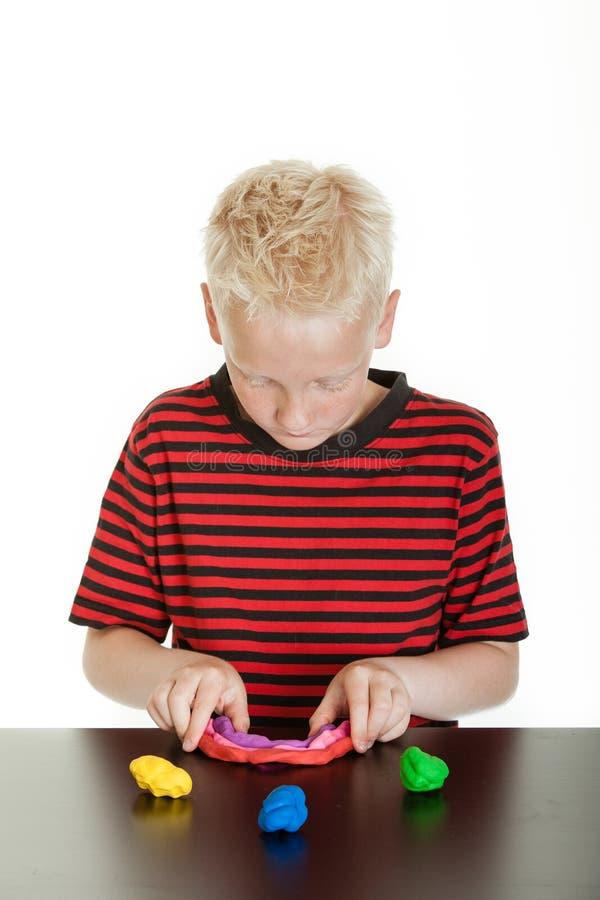 Het creatieve jonge jongen spelen met plastic stopverf royalty-vrije stock foto