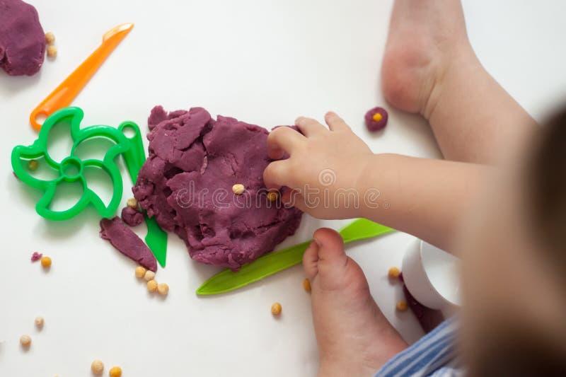 Het creatieve meisje spelen met kleurrijke modelleringsklei bij kleuterschool Weinig jong geitje die thuis vormen Ontwikkelingssp royalty-vrije stock foto's