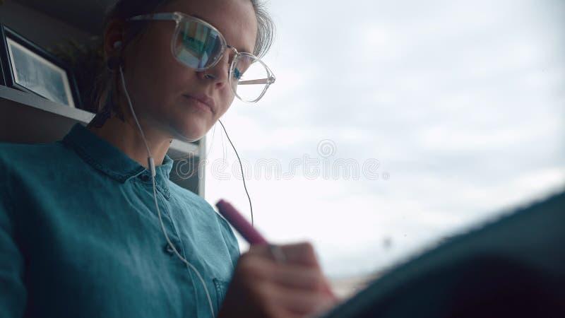 Het creatieve meisje zit op vensterbank luistert aan muziek, trekt in notitieboekje royalty-vrije stock afbeeldingen