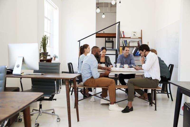 Het creatieve team komt bij een lijst in een bureau, één gebruikend samen telefoon royalty-vrije stock afbeeldingen