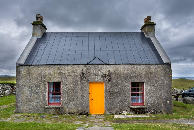 Het croft huis whitehouse, met oranje deur en donkerrode vensters, op een stormachtige, bewolkte dag royalty-vrije stock fotografie
