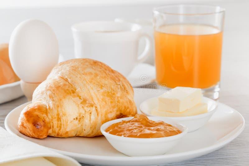 Het croissant, gekookt ei, drukte sap, vers koffie of thee met melk, boter, jam Continentaal Frans Ontbijt royalty-vrije stock foto