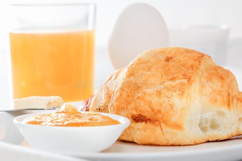 Het croissant, gekookt ei, drukte sap, vers koffie of thee met melk, boter, jam Continentaal Frans Ontbijt royalty-vrije stock afbeeldingen