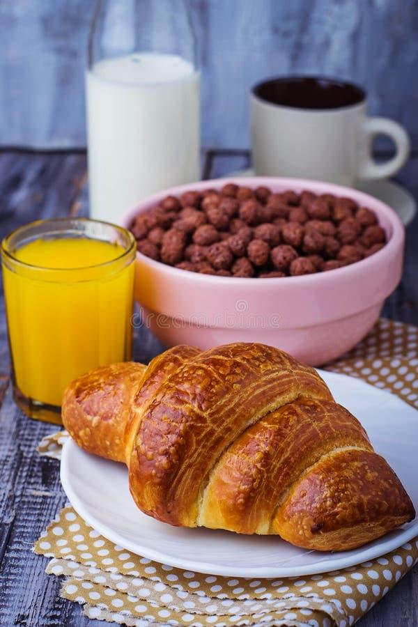 Het croissant, graangewassenvlok, koffie, melk, jus d'orange, kookte ei stock foto