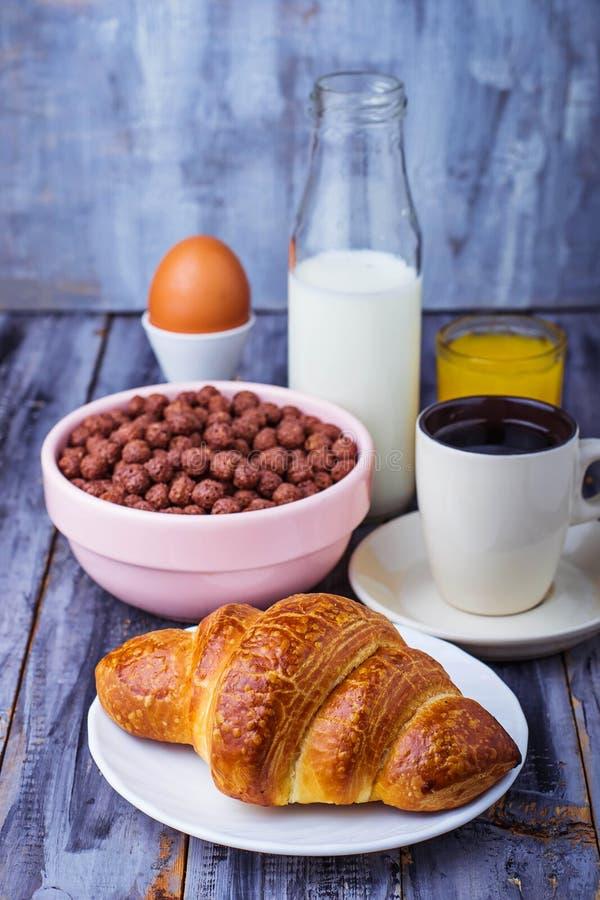 Het croissant, graangewassenvlok, koffie, melk, jus d'orange, kookte ei stock afbeeldingen