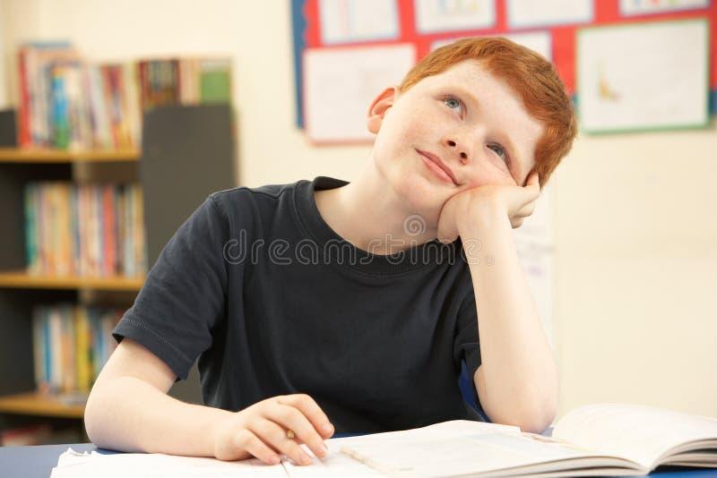 Het Dagdromen van de schooljongen in Klaslokaal stock afbeelding