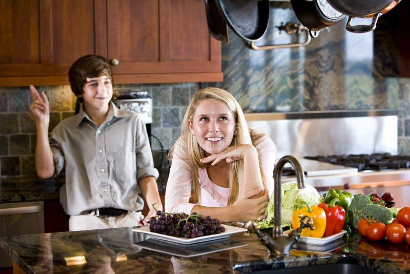 Het dagdromen van de tiener in keuken met broer stock afbeeldingen
