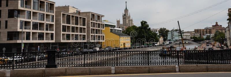 Het dagelijkse leven van een moderne stad Weergeven van de brug aan de weg langs de waterkant, die heel wat auto's drijft Bouw en royalty-vrije stock afbeelding