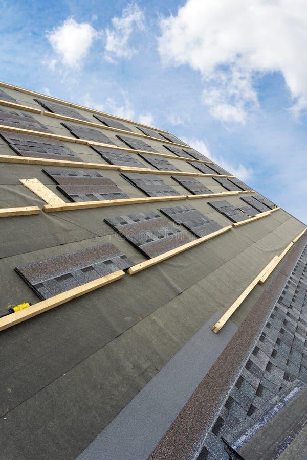 Het dak van de asfalttegel op nieuw huis in aanbouw royalty-vrije stock afbeelding