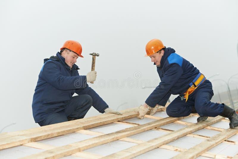 Het dak van de de arbeidershamer van het dakwerk het inschepen royalty-vrije stock afbeeldingen