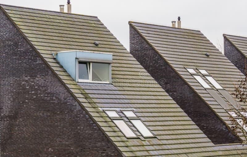 Het dak van een moderne Nederlandse driehoek vormde huis, nieuwe ontworpen architectuur, koekoeken met dak het betegelen, huizen  royalty-vrije stock afbeeldingen
