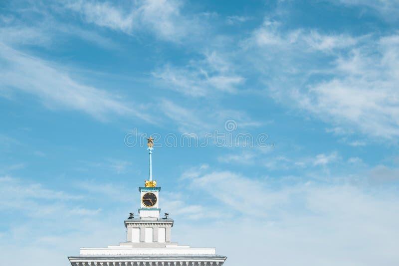 Het dak van een oud gebouw met een grote klok met een ster op de toren stock fotografie