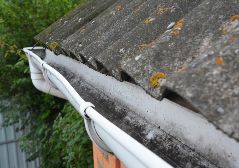 Het dak van het huisasbest met de plastic pijp van de dakgoot Huis het guttering met houders stock fotografie
