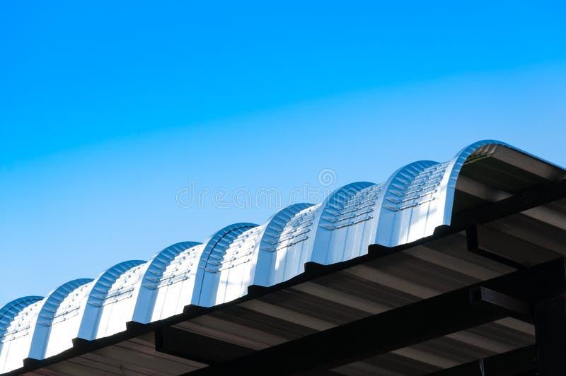 Het dakkromme van het metaalblad op blauwe hemel, Moderne bouw stock afbeelding