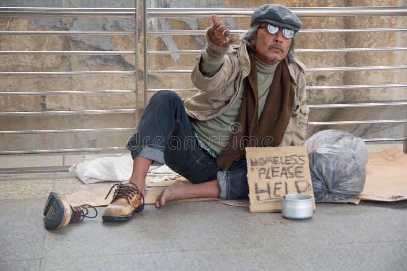 Het dakloze hogere volwassen mens zitting en bedelen royalty-vrije stock foto