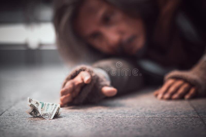 Het dakloze mensenbereik deelt aan geld op de vloer uit royalty-vrije stock afbeelding