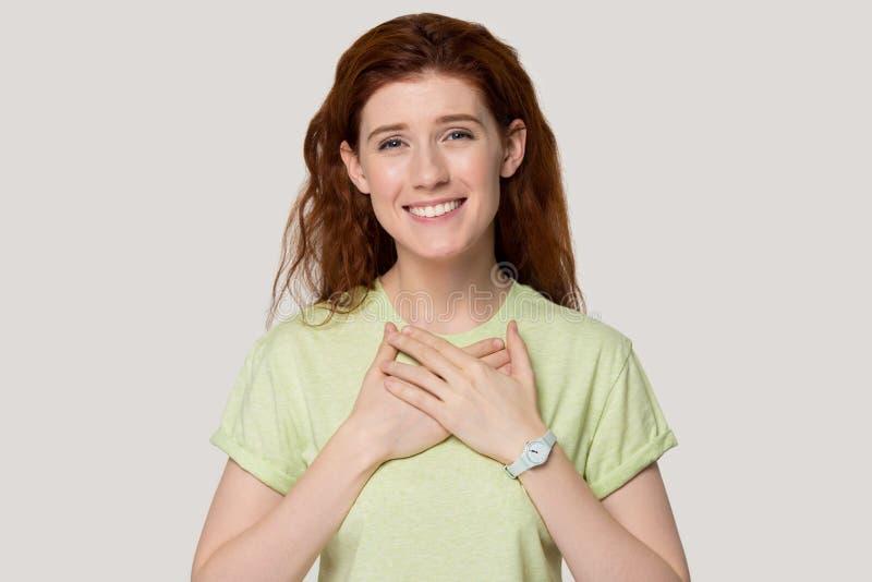 Het dankbare roodharige meisje met handen op borst voelt dankbaar stock afbeelding