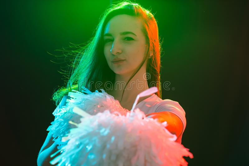 Het dansen, sport, mooi en mensenconcept - het jonge cheerleadermeisje in duisternis toont pom poms en glimlach royalty-vrije stock afbeelding