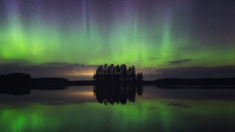 Het dansen van de noordelijke lichten Aurora borealis in de herfst op een prachtig meer en eiland 's nachts royalty-vrije stock fotografie