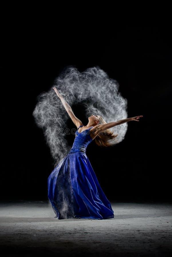 Het dansende meisje in dark, maakt kunstprestaties met witte stofwolk royalty-vrije stock afbeelding