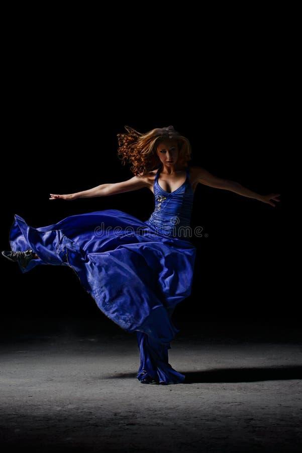 Het dansende meisje in de duisternis, voert pirouetten uit royalty-vrije stock afbeeldingen