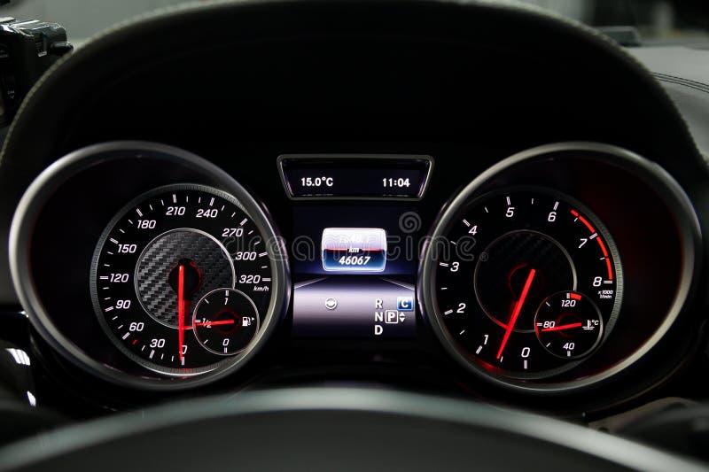 Het dashboard van de auto gloeit blauw en rood bij nacht met een snelheidsmeter, koolstof en tachometer en andere hulpmiddelen om stock foto's